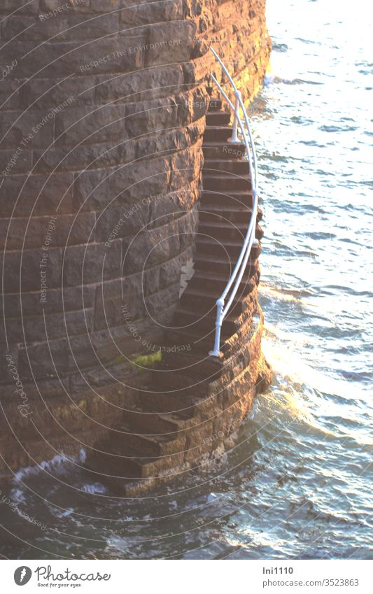 leicht gebogene schmale Steintreppe mit Geländer führt im Abendlicht an Kaimauer hinunter ins Meer steil tief gefährlich Notaufstieg Rettungstreppe Treppe