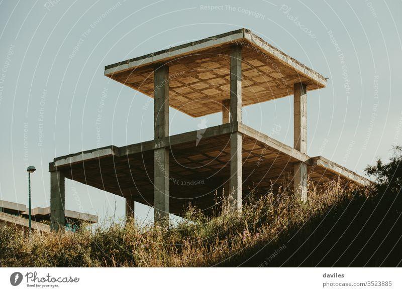 Hausbetonfundament auf der Spitze eines Hügels. Aufgegebene Konstruktion. Konzept zur Wohnungs- und Immobilienkrise. Landschaft heimwärts Krise Finanzen