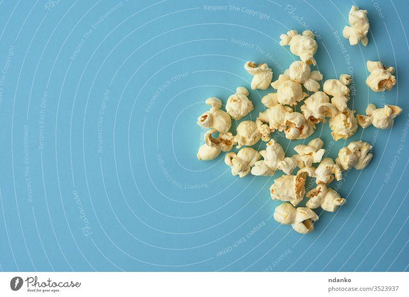 weißes köstliches Popcorn auf blauem Hintergrund, ein Platz für eine Inschrift Overhead Popkorn Salz gesalzen salzig Ernährung oben klassisch Nahaufnahme Farbe