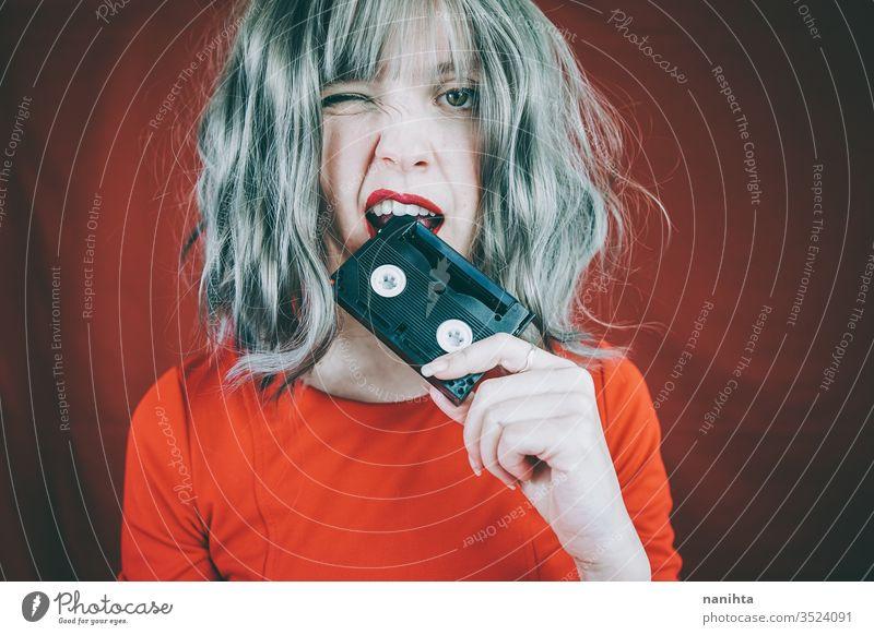 Künstlerisches Porträt mit einem Modell, das sein Gesicht mit einem Retro-Videoband bedeckt retro altehrwürdig Kassette Klebeband rot Frau sexy hübsch Musik