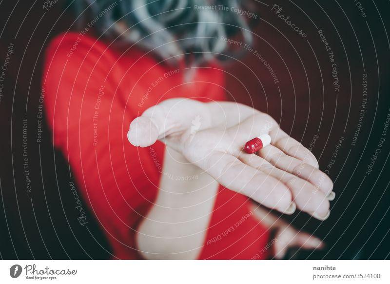Junge Frau hält in der Hand eine weiß-rote Pille Tablette Medikament Medizin Virus Süchtige süchtig machend Sucht Schmerztablette Schmerzmittel abschließen