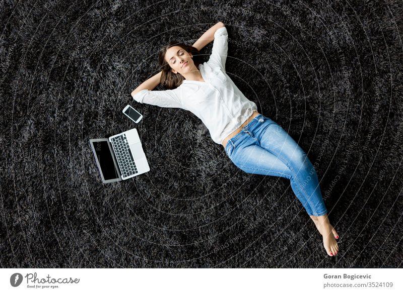 Junge Frau liegt auf dem Teppich Verlegung legen Rücken Laptop Stock Mädchen Telefon charmant Freizeit Ansicht rot Europäer Erwachsener Menschen Kaukasier