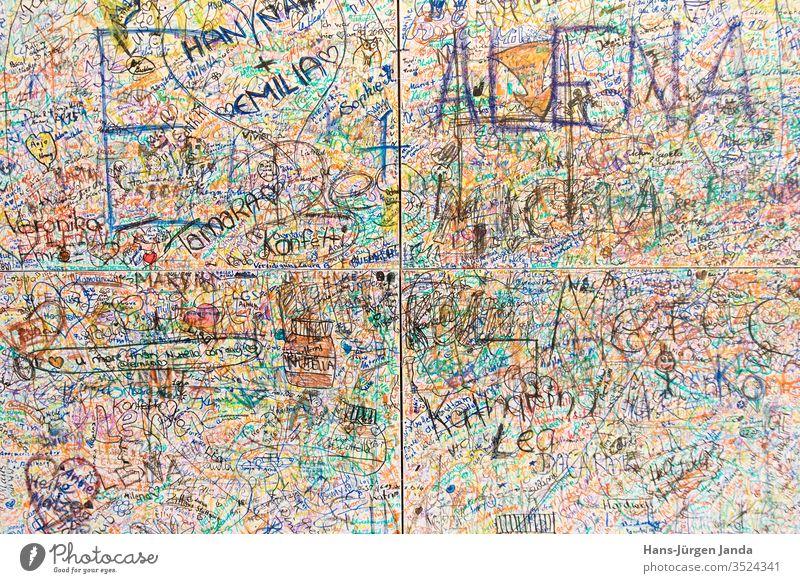 Wand mit vielen Namen und Texten wirr durcheinander text wand wort namen unterschrift nachricht bunt hintergrund farbig filsstift herz verewigt hinterlassen
