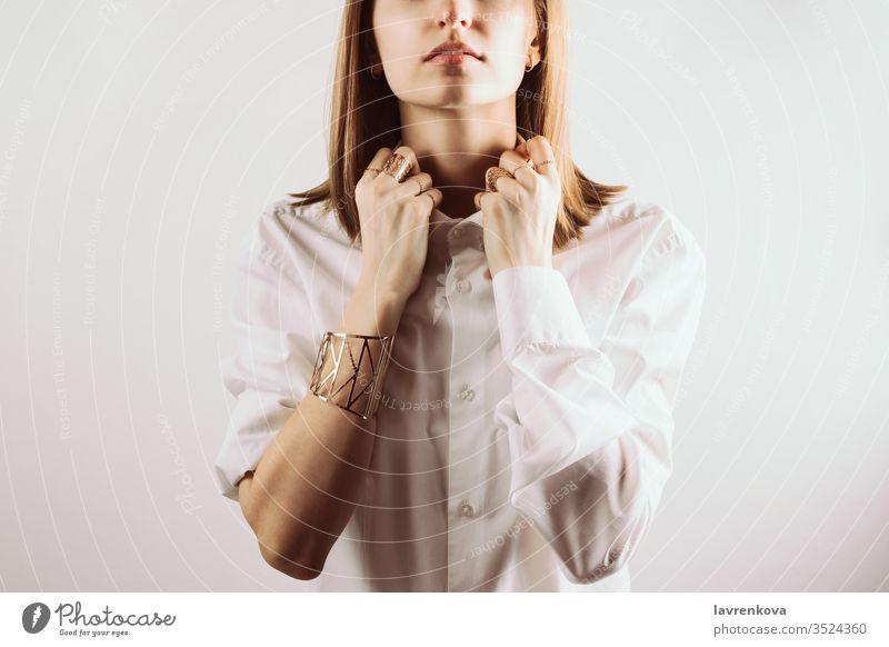 Porträt einer jungen erwachsenen Frau, die mit ihren Händen einen Kragen eines weißen Hemdes hält, selektiver Fokus Ringe gesichtslos Schmuck Atelier Armband