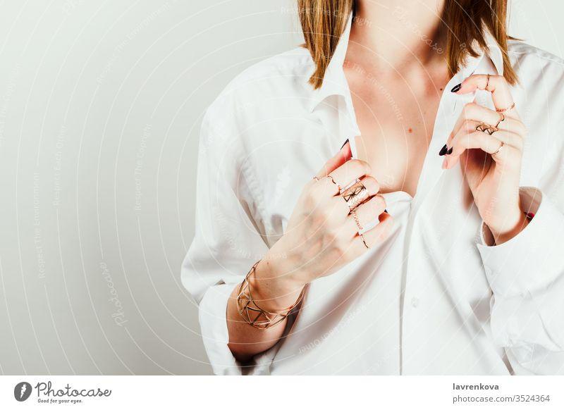 Gesichtsloses Porträt einer jungen erwachsenen weißen Frau in weißem Hemd, die die Seiten ihres Hemdes hält. Selektiver Fokus. golden Haut Fröhlichkeit Atelier