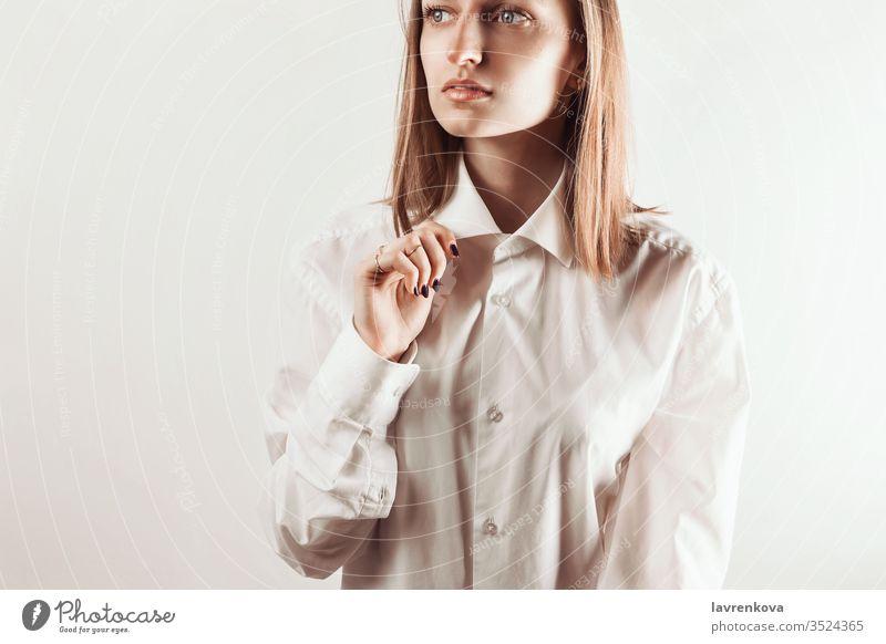 Porträt einer jungen erwachsenen Frau, die mit der Hand einen Kragen eines weißen Hemdes hält, selektiver Fokus Aussehen saubere Haut Naturkosmetik Maniküre