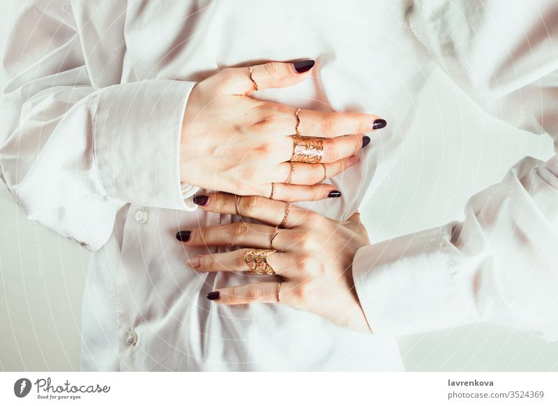 Nahaufnahme der Hände einer weißen Frau mit verschiedenen Ringen um ihre Warten, weißes Hemd, weißer Hintergrund, selektiver Fokus. gestikulieren Dekor Reichtum