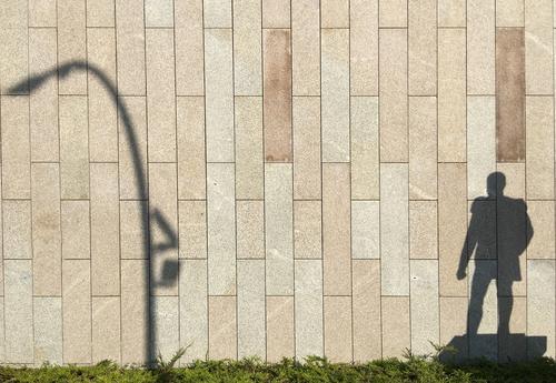 Schatten eines Denkmals und einer Laterne an der Wand Fassade Schattenspiel Licht Mann Mauer Außenaufnahme Tag Menschenleer Farbfoto Architektur Haus Stadt