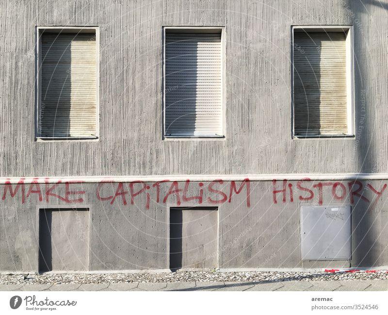 Graue Hauswand mit geschlossen Fensterläden und Aufschrift grau Kapitalismus Make capitalism history Kritik Fassade Spruch Slogan Wand Menschenleer Mauer