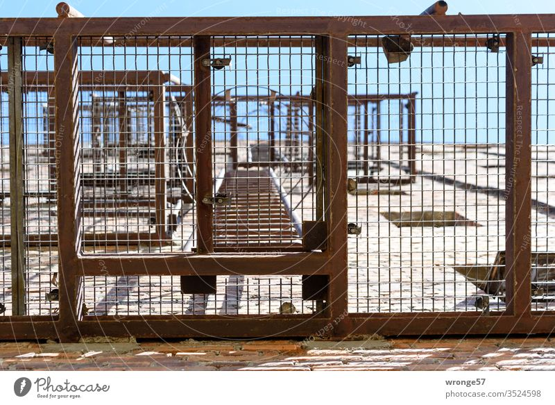 Blick durch das Podest einer stählernen Feuerleiter himmelwärts Fluchtleiter Fluchttreppe Froschperspektive Gitterrost Hauswand Giebelseite Notfall Fluchtweg