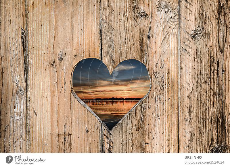 ausgesägtes Herz in einer Holzbretterwand mit Einblick zum Sonnenuntergang am See Bretterwand Durchblick herzig Struktur strukturiert Landschaft Nahaufnahme