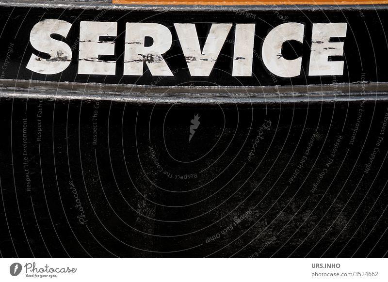 weißer Schriftzug SERVICE in Großbuchstaben auf schwarzem Hintergrund Service Text Aufschrift Schriftzechen Schiffsrumpf Boot schmutziz Buchstaben