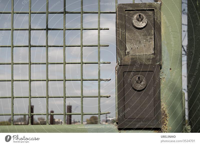Türschlösser an einem grünen Metalltor mit Gitter Türschloss Schloss Schlösser Gitternetz verschlossen versperrt gesperrt zugesperrt kein Durchgang geschlossen