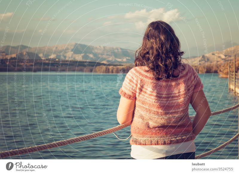 Frau, die auf das Seeufer starrt, Rückenporträt einer Frau, die am Dock zum Horizont blickt Tag Außenaufnahme Natur Landschaft Wasser Reflexion & Spiegelung