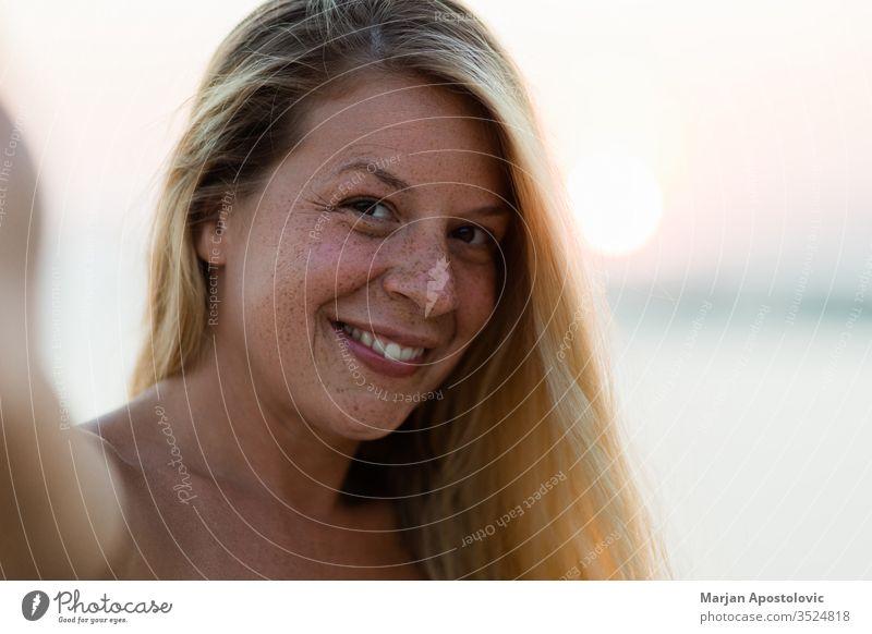Junge gebräunte Frau bei Sonnenuntergang ein Selfie Erwachsener attraktiv Strand schön Schönheit blond Fotokamera sorgenfrei lässig Kaukasier heiter Teint