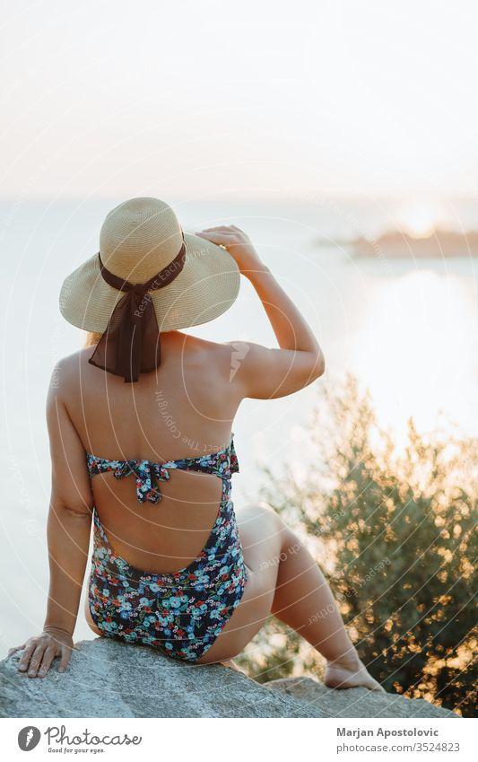 Junge Frau genießt Sonnenuntergang am Meer Abenteuer schön Schönheit sorgenfrei Klippe Küste Küstenstreifen Küstenlinie genießend Abend Freiheit Mädchen Hut