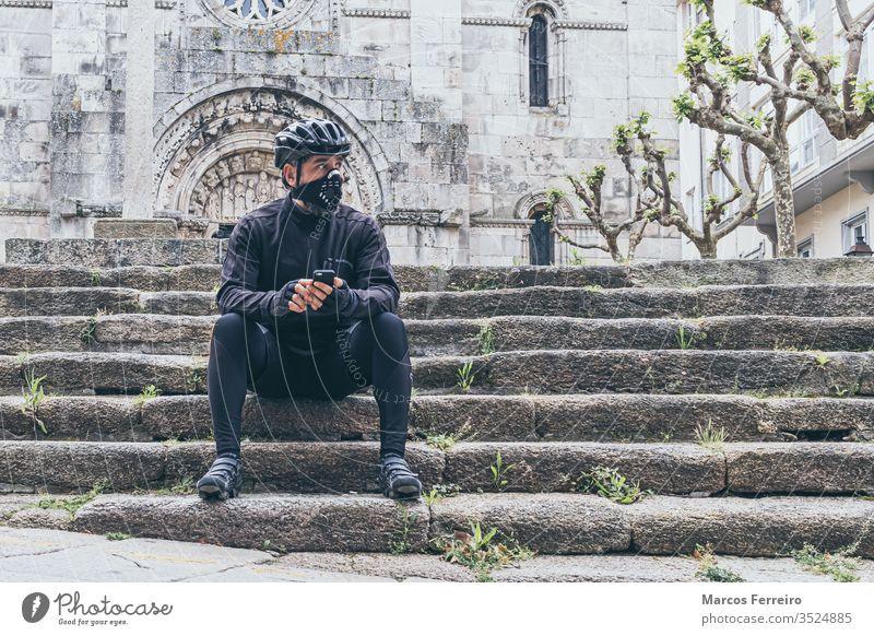 erwachsener Mann mit Fahrradkleidung und Maske in der Stadt Sport Viren Corona-Virus Atemwegserkrankungen Gesichtsmaske außerhalb COVID Kaukasier