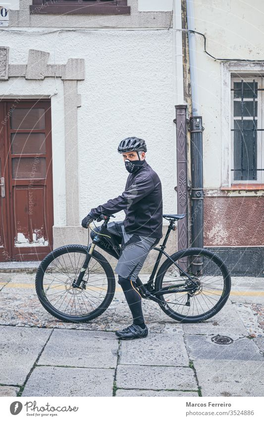 erwachsener Mann mit Fahrrad in der Stadt mit Maske Sport Viren Corona-Virus Atemwegserkrankungen Gesichtsmaske außerhalb COVID Kaukasier Gesundheitswesen