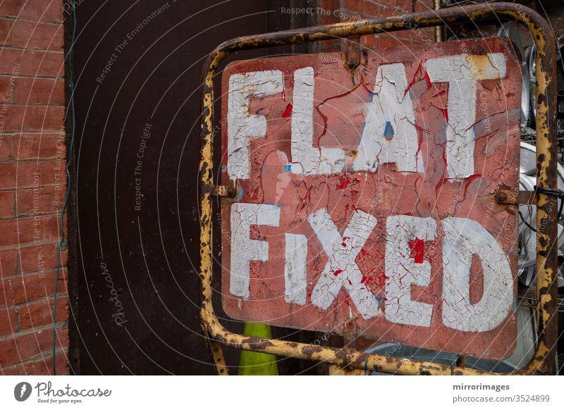 Verzweifelter Alter repariert einen platten Reifen Rot-weißes Schild altes verwittertes flaches festes Schild flach fixiert einen platten Reifen reparieren