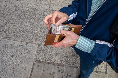 Mann, der seine Brieftasche öffnet, um etwas Bargeld in amerikanischer Währung auszugeben Wirtschaft und Finanzen Barzahlung Wirtschaft und Zahlungen