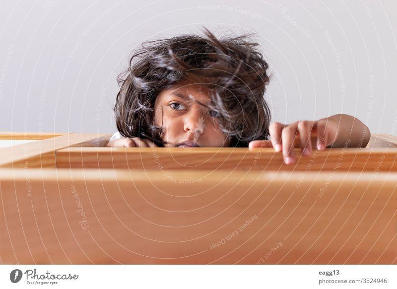 Ein Mädchen steht auf dem Kopf und schaut vom oberen Ende ihrer Koje nach unten Jugendzeit bezaubernd allein Bett Streu Schlafzimmer Schlafenszeit braune Haare