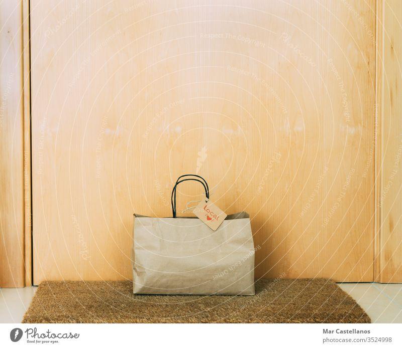 Einkaufstasche aus Papier mit Kartonaufkleber an der Haustür des Hauses. Konzept des Einkaufens. Tasche kennzeichnen Tür Eingang Unterlage recycelbar Verkauf