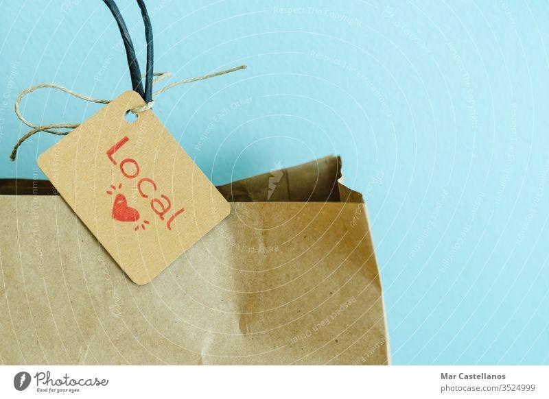 Einkaufstasche aus Papier auf blauem Hintergrund. Etikett mit Herz und Text LOCAL. Einkaufskonzept. kaufen Tasche kennzeichnen Blauer Hintergrund recycelbar