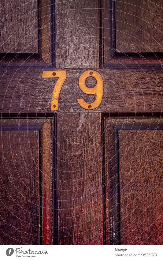 Hausnummer 79 an einer dunklen hölzernen Haustür 79 Zahl Adresse gealtert britannien klassisch stilvoll abschließen Nahaufnahme dunkel Dekoration & Verzierung