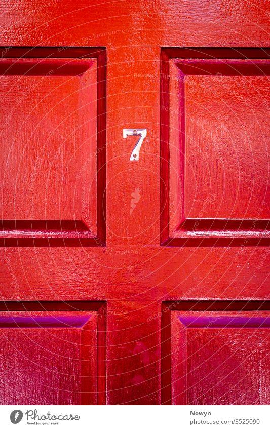 Hausnummer 7 an einer roten Holzhaustür mit Glück 7 Zahl Adresse britannien Burgunder klassisch stilvoll abschließen Nahaufnahme Textfreiraum copyspae