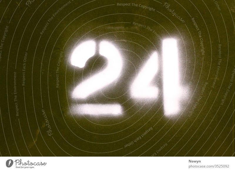 Nummer 24 auf eine grüne militärische Metalloberfläche gesprüht 24 Nummer Armee britannien abschließen Nahaufnahme Detailaufnahme Ziffer Ziffern Tür Außenseite