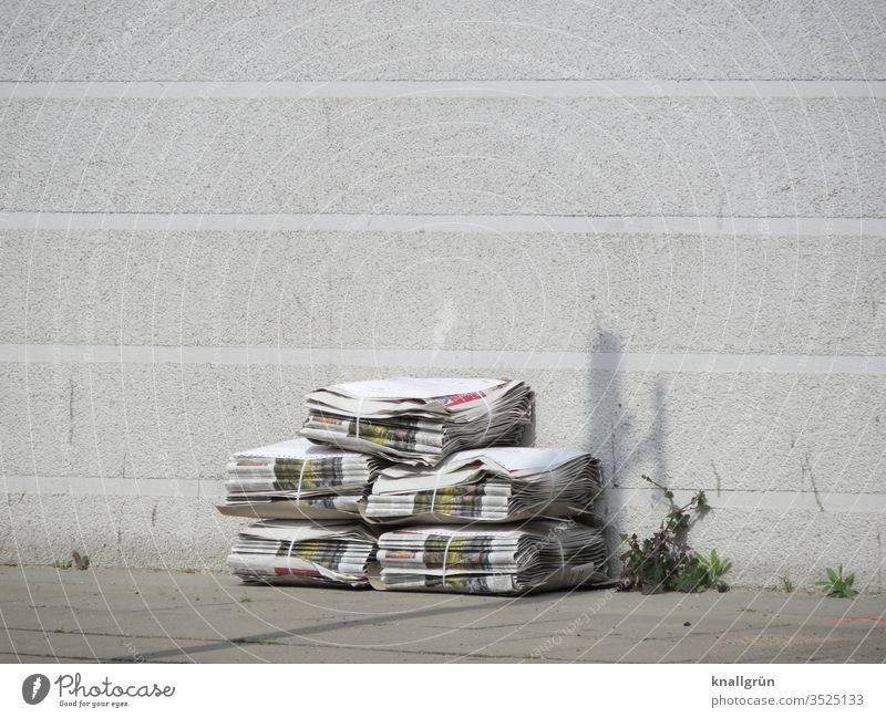 Fünf Packen Zeitungen gestapelt auf dem Gehweg vor einer weißen Hauswand, daneben etwas Unkraut aus einer Fuge wachsend Printmedien Stapel zusammengebunden