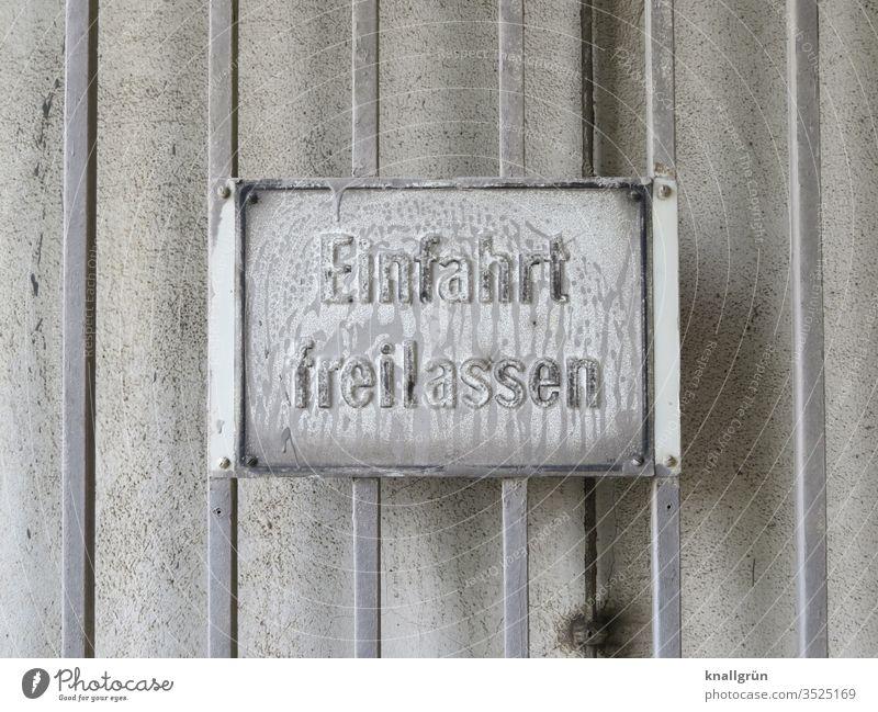 """Weiß überpinseltes """"Einfahrt freilassen""""- Schild auf weiß gestrichener Metallwand Schilder & Markierungen Kommunizieren Hinweisschild Warnschild Außenaufnahme"""