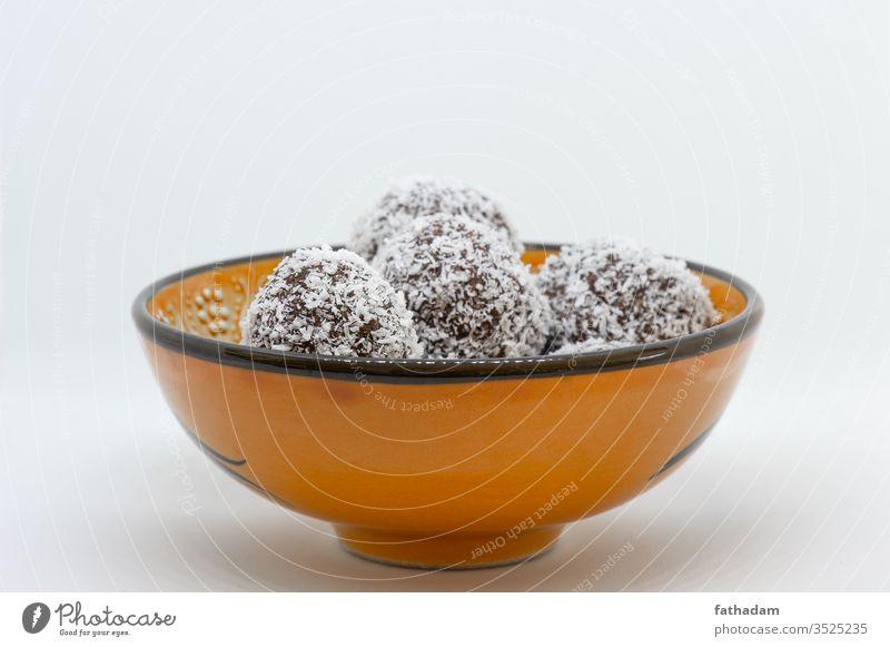 Kokosnusskugeln in einer orangefarbenen Kugel Hintergrund Ball Bälle Schalen & Schüsseln braun coco Kokoskugel Keks lecker Dessert Lebensmittel selbstgemacht