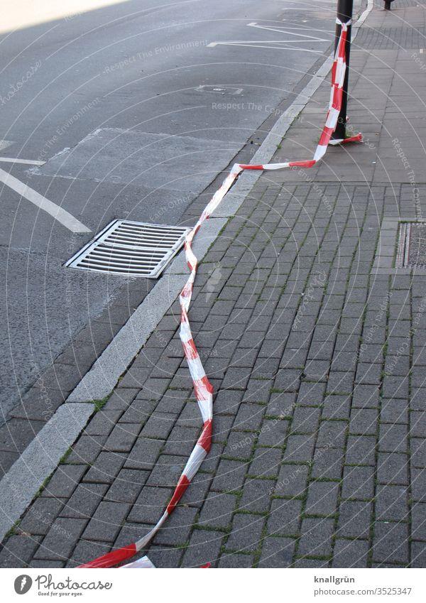 Flatterband entlang der Strasse und dem Bürgersteig auf dem Boden liegend Absperrung Straße Markierungslinie Gully Pflastersteine Fahrbahnrand Rinnstein