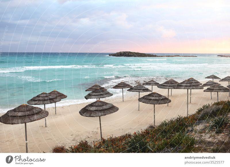 schöne Strohschirme am Strand am leeren Strand,,strahlend blaues Wasser und blauer Himmel,,paradiesischer tropischer Strand,,entspannende Zeit,,erstaunliche Aussicht,,keine Menschen,,Sonnenuntergang Hintergrund. selektiver Fokus