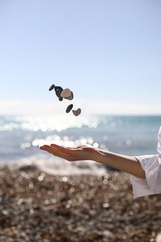weibliche Hand wirft einen Kieselstein in die Hand vor dem Hintergrund des blauen Himmels, des Strandes und des Meeres. platz für text. Frau MEER Mädchen