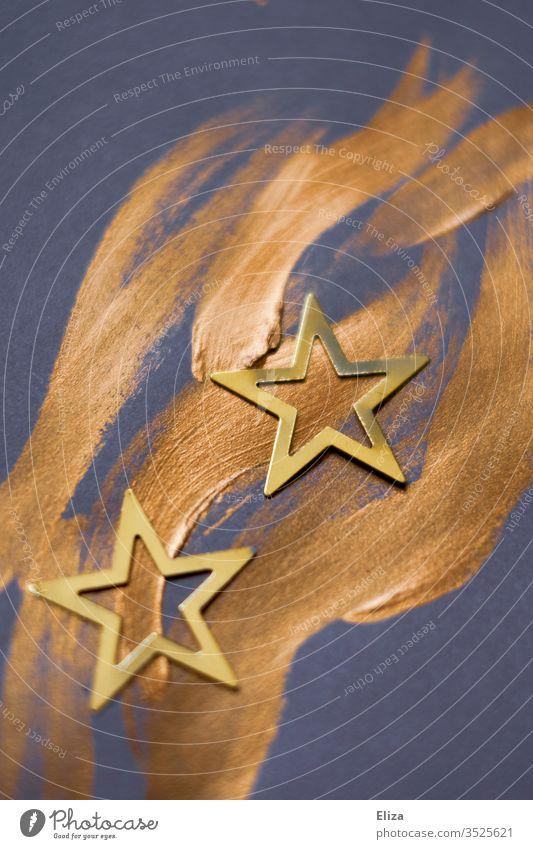Zwei Sterne auf goldenen wellenförmigen Pinselstrichen. Weihnachten. Golden Sternr Weihnachtsstern gemalt Weihnachtsdekoration weihnachtlich blau lila violett