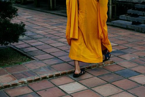 Ein buddhistischer Mönch in traditionellem orangefarbenen Gewand Buddhismus Religion & Glaube Asien Kutte Mönchskutte Ti-cîvara gehen Füße nackt Sandalen