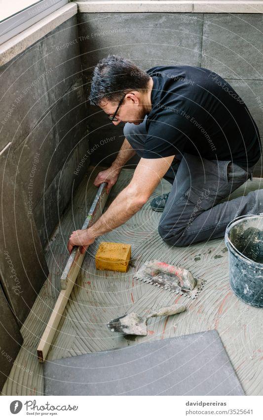 Maurer-Prüfboden mit einer Ebene Handwerker Nivellierung Überprüfung Boden Kacheln Renovierung sicherstellen Niveau Zement-Fliesenimitation verglaste Terrasse