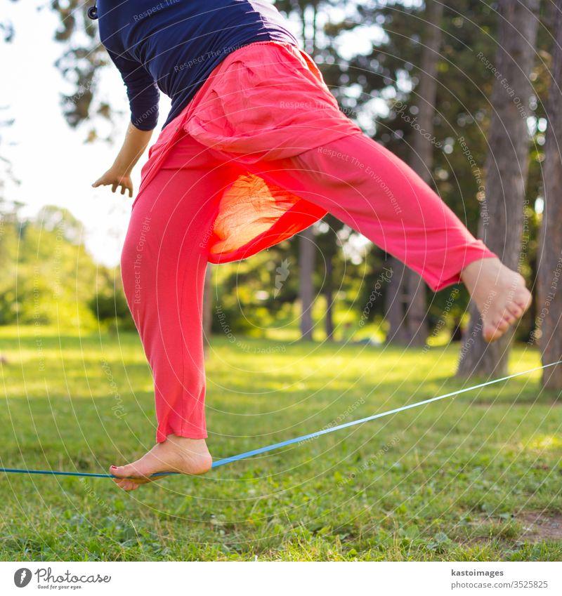 Slackline im Stadtpark. Schlaffleitung Aktivität Sport Gleichgewicht schlaff Linie Drahtseil jung Person Seil Fitness Rücken Natur Konzentration passen laufen