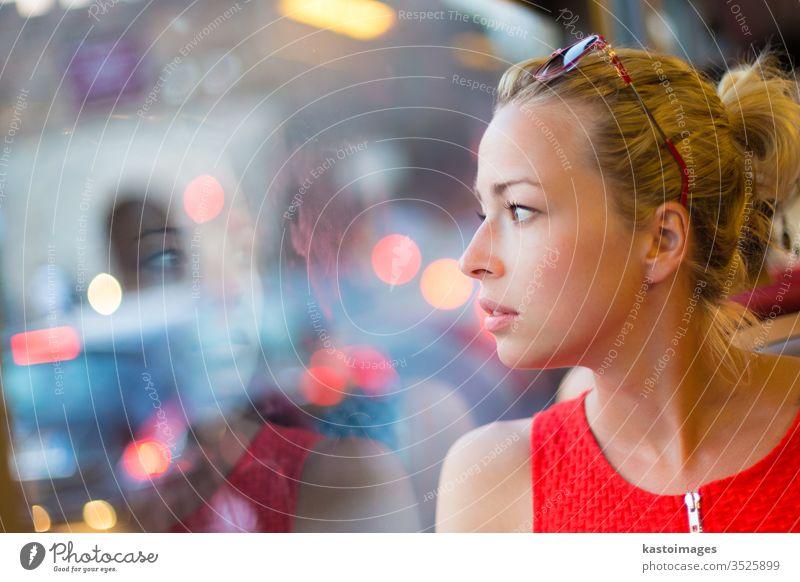 Frau schaut aus dem Fenster der Straßenbahn. Verkehr Porträt reisen Bus urban Ansicht beobachten lässig Mode nachdenklich modern Streetstyle Ausflug Sitzen