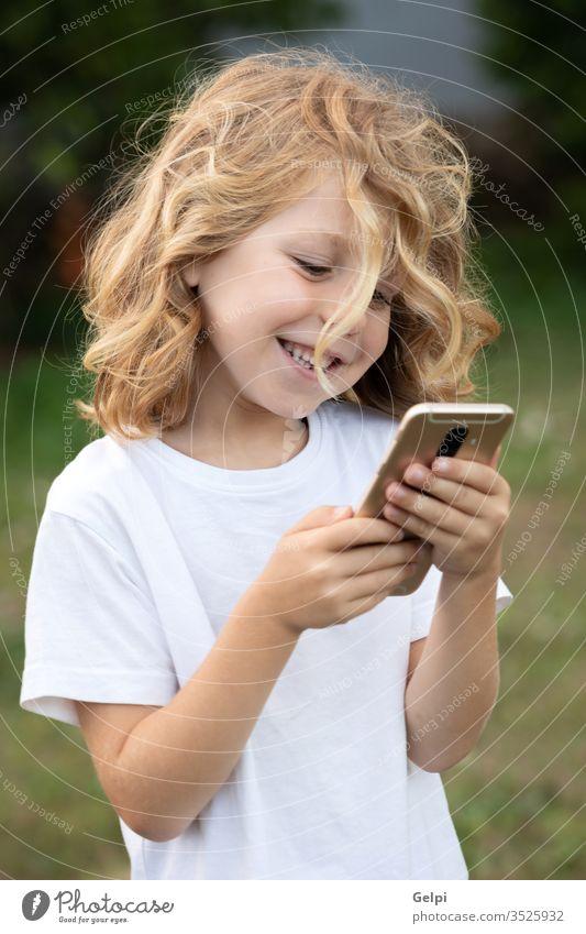 Lustiges Kind mit langen Haaren, das ein Handy hält. Telefon Park Freizeit Funktelefon Kindheit Smartphone Lifestyle Junge blond Mitteilung Anschluss
