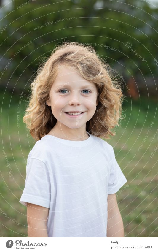 Lustiges blondes Kind mit langen Haaren. außerhalb eine Kindheit Menschen Kaukasier Freude Junge wenig Natur Behaarung wellig spielen Sommer jung im Freien Spaß