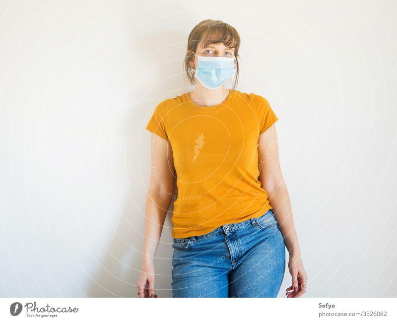 Junge Frau mit schützender Gesichtsmaske Mundschutz COVID19 Coronavirus Quarantäne zu Hause bleiben allein Schutz Isolation Seuche Virus Grippe Mädchen