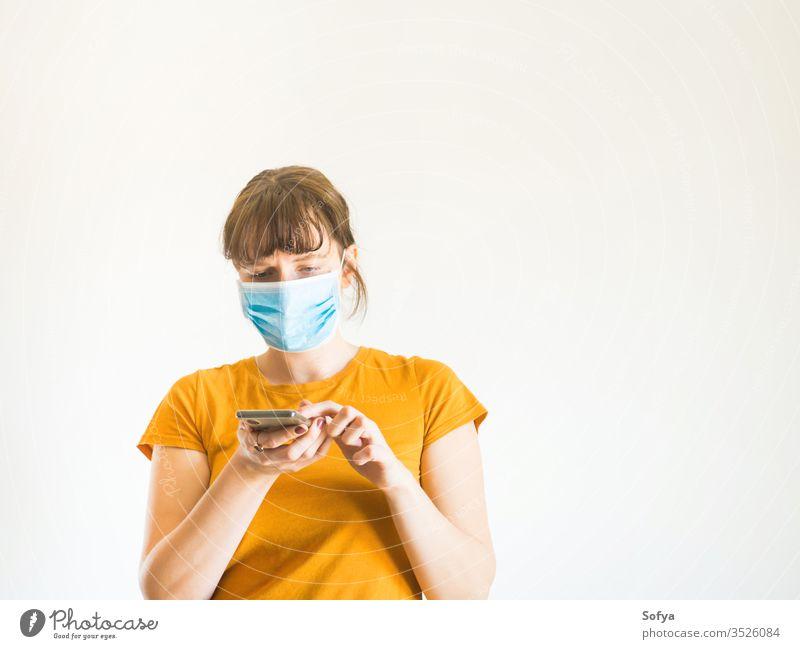 Junge Frau mit Gesichtsmaske und Smartphone Mundschutz COVID19 benutzend Mobile Telefon digital Anruf Hotline Helpline abstützen Coronavirus Person Quarantäne