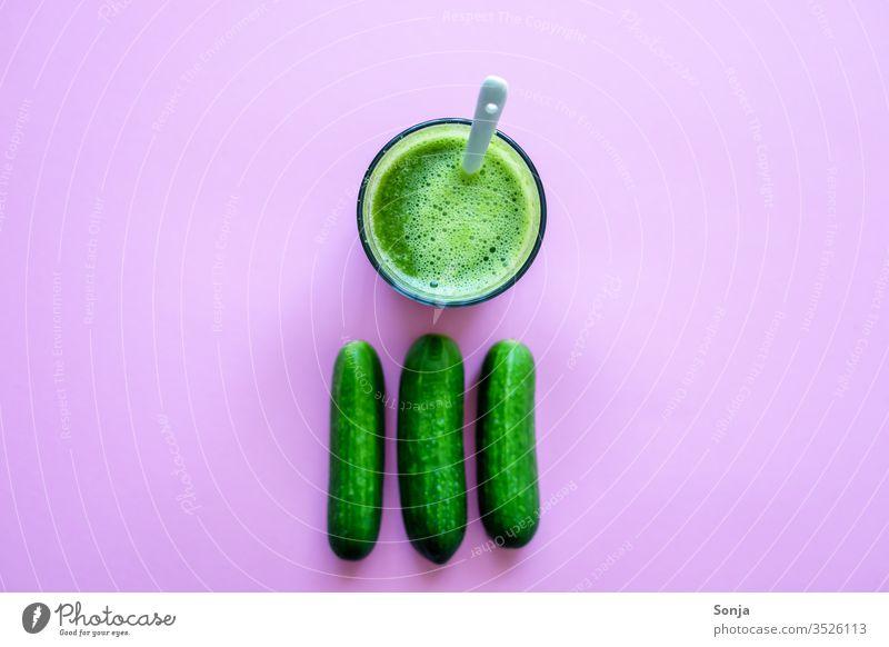 Frischer Gurkensaft in einem Glas und ganze Gurken auf einem rosa Hintergrund, Draufsicht klein Saftglas smoothie grün Detox Gesunde Ernährung Getränk Diät