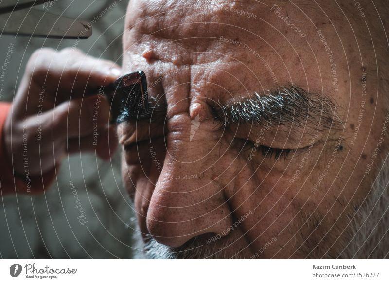Älterer lässt sich im Badezimmer die Augenbraue stutzen Mann Kopf Vollbart Behaarung Damenbart Person Gesicht Holunderbusch alt Menschen älter Stirn Erwachsener
