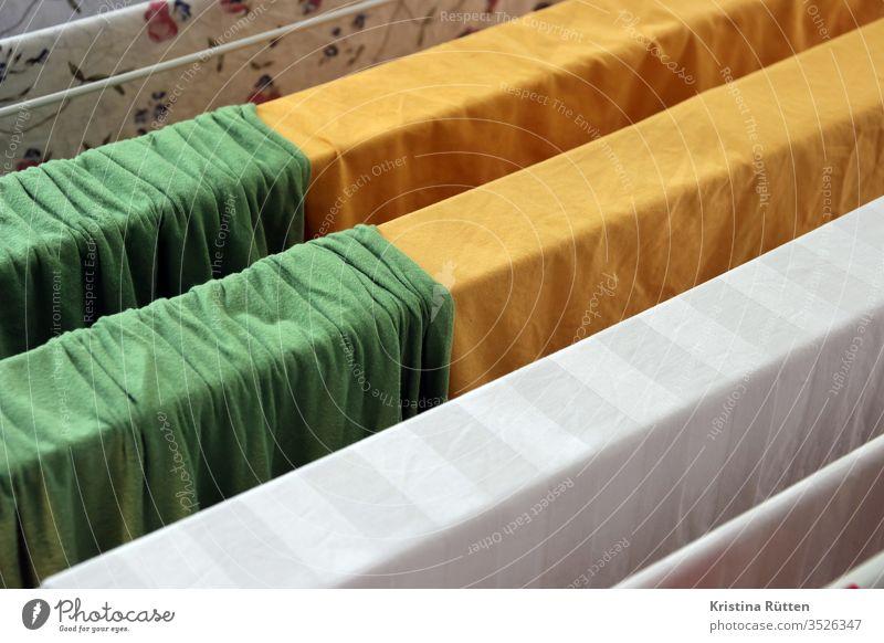 bettwäsche hängt zum trocknen auf dem wäscheständer bettlaken waschtag waschen sauber frisch trocken bunt farbig grün gelb weiß stoff textil gewebe baumwolle