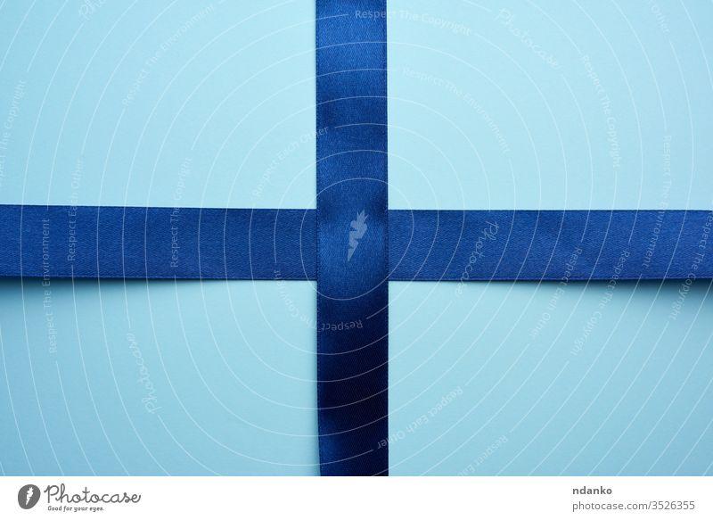 blaues Seidenband gekreuzt auf blauem Hintergrund präsentieren Bändchen Satin Form Glanz abstrakt Jahrestag Geburtstag Feier Weihnachten klassisch Nahaufnahme