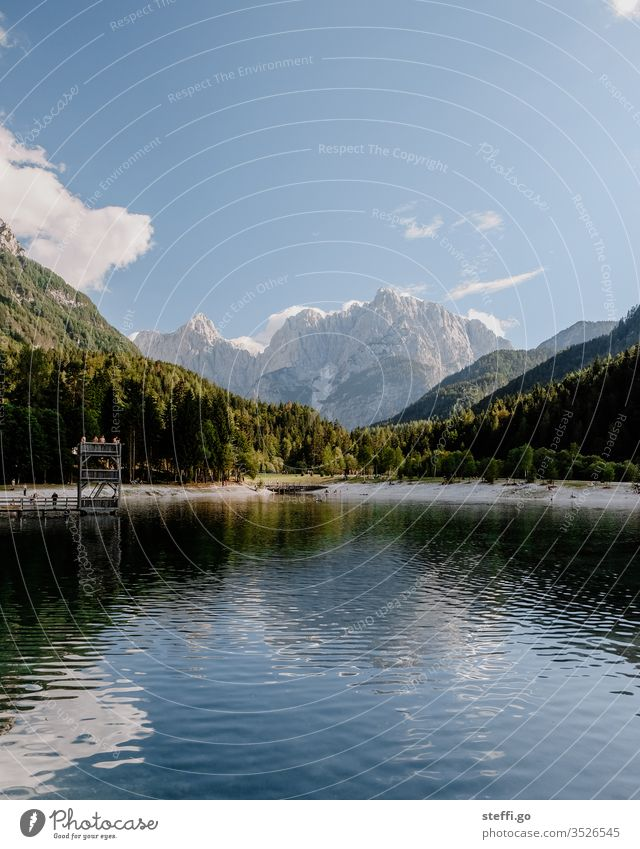 See umrahmt von Bergen im Sommer Bergkette Ausflugsziel Ferne Seeufer ruhig Felsen Freiheit wandern Erholung Wolken Tourismus Abenteuer Ferien & Urlaub & Reisen